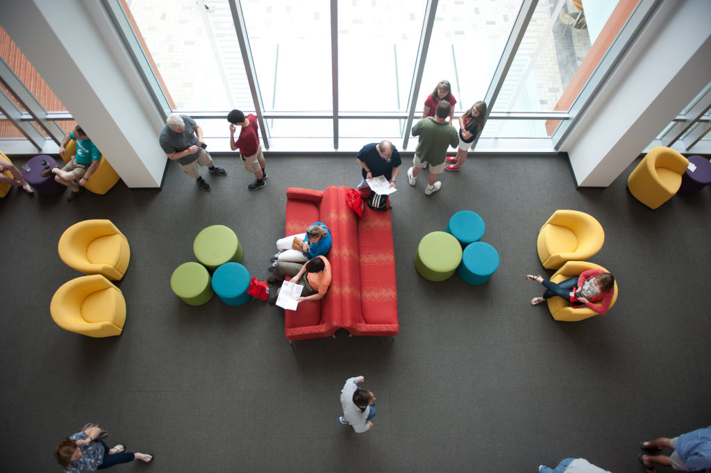 Students working, collaborating, and passing through a casual lounge space in Talley Student Union.