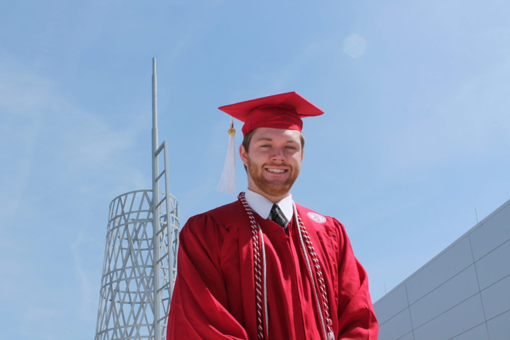 A recent graduate poses in front of Talley Student Union in full regalia.