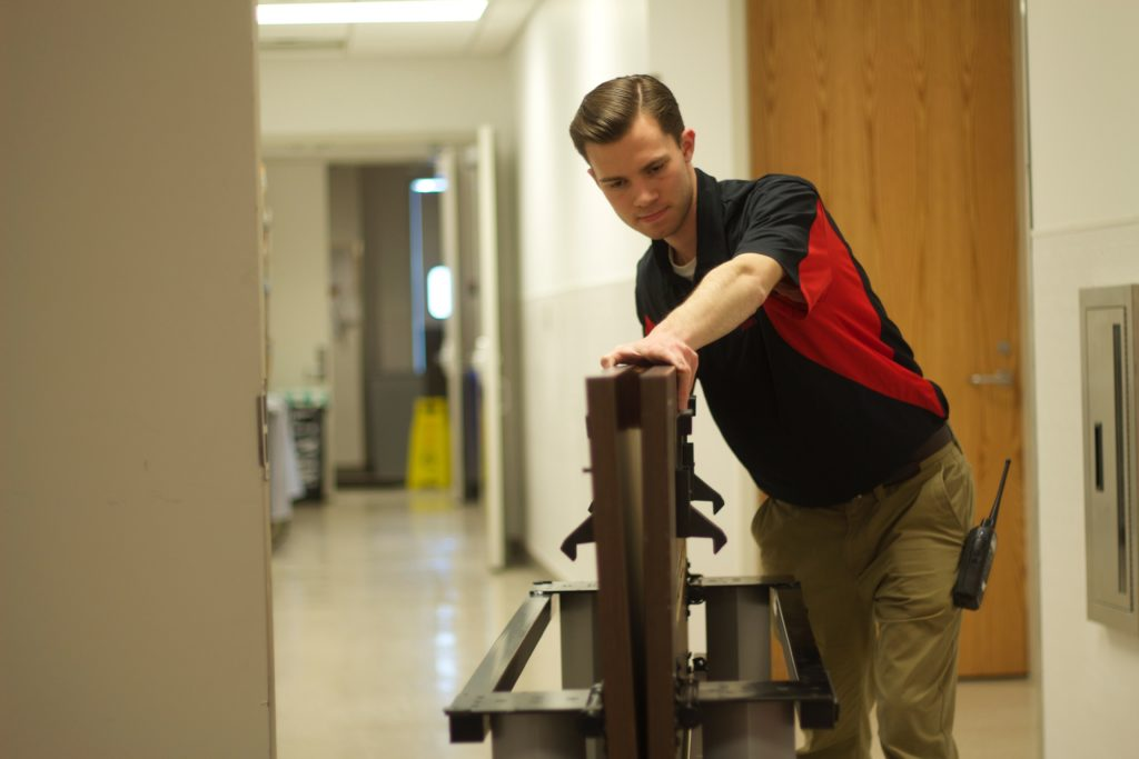 A student employee moves equipment for event setup at the student center.