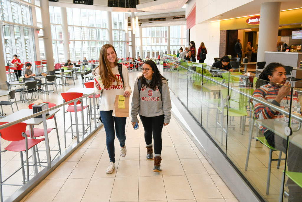 Two students walk through the Talley Pavillions dining area.
